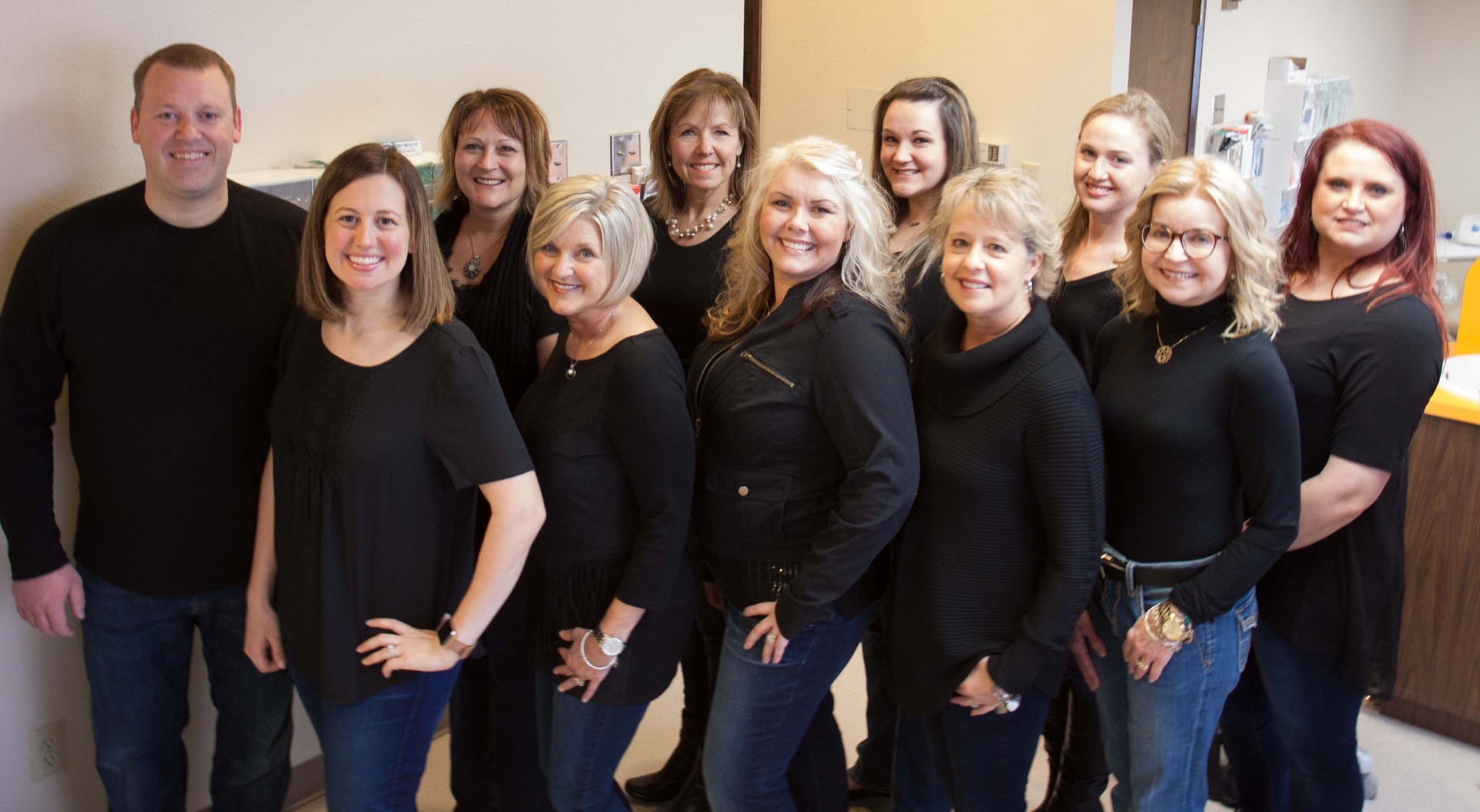 10 women and one man smiling, all in black shirts. Entire staff of Todd S. Johnson dental office.